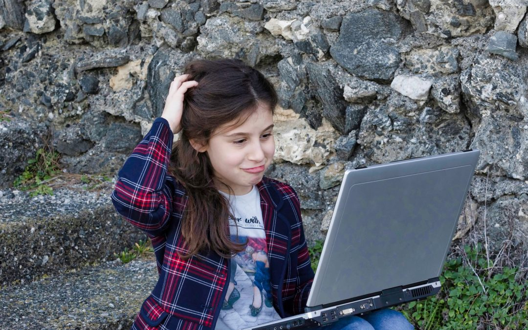 Puzzled 11+ girl with laptop